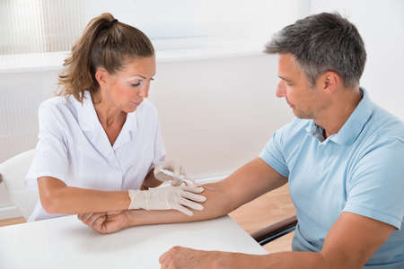 body blood: Portrait Of Doctor Drawing Blood  From Patient With Syringe In Hospital Stock Photo