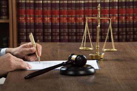 Cropped image of male judge writing on legal documents at desk in courtroom Banque d'images