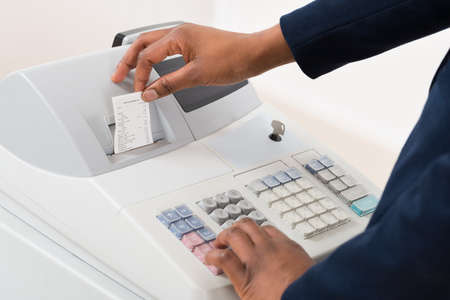 sales person: Close-up Of A Sales Person Operating Cash Register