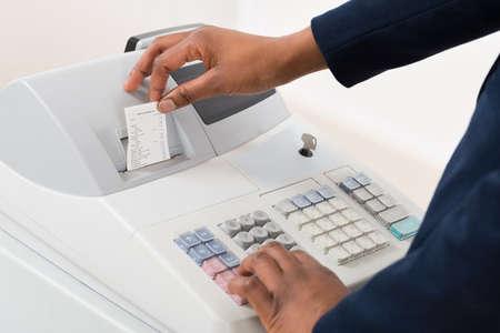cash: Primer plano de una persona de ventas de funcionamiento de la caja registradora