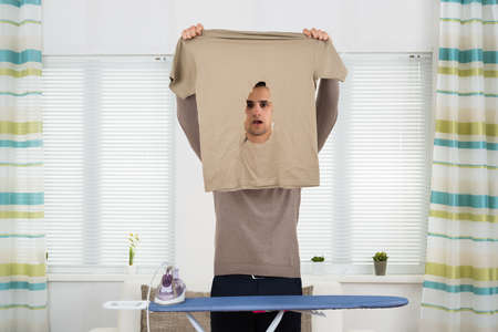 iron curtains: Shocked young man looking at burnt tshirt while standing by ironing board at home