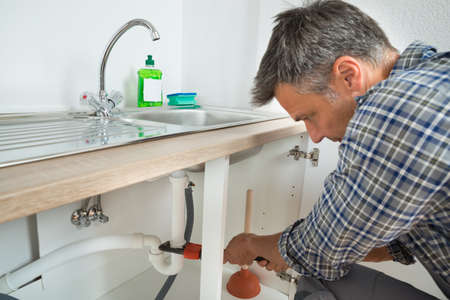 Home repair: Male plumber fixing sink pipe with adjustable wrench in kitchen