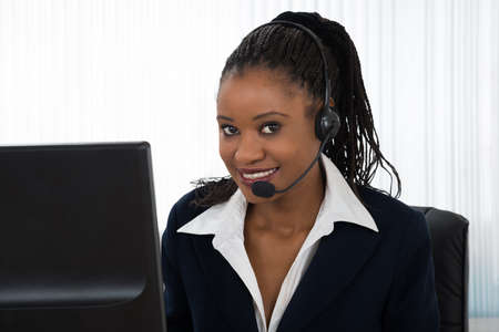 Portrait Of A Young Smiling Businesswoman Talking On Headset