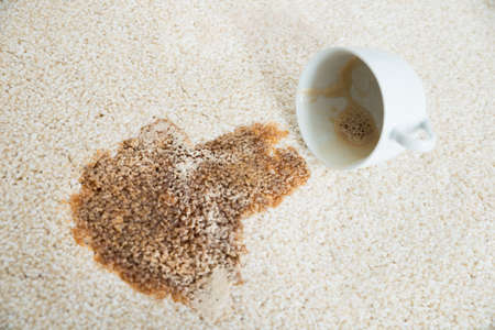carpet stain: Close-up of coffee spilling from cup on carpet