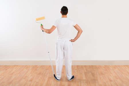 pintor: Vista trasera de hombre joven con el rodillo de pintura mientras est� de pie contra la pared blanca en casa