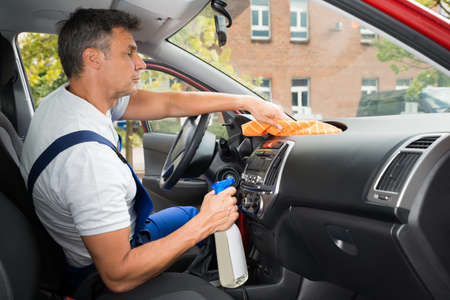 wash car: Side view of mature male worker cleaning car interior Stock Photo