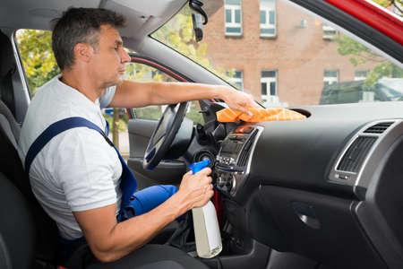 autolavaggio: Vista laterale del maturo maschio pulizia lavoratore auto interni