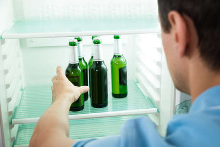 tomando refresco: Vista lateral de un joven quitar la botella de cerveza de la nevera en casa
