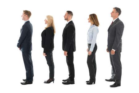 fila de personas: vista lateral de cuerpo entero de la gente de negocios de pie en fila sobre fondo blanco Foto de archivo