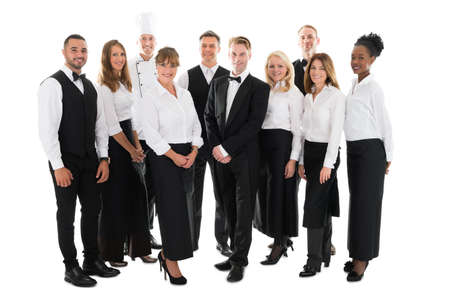 Full length portrait of confident restaurant staff standing in row against white background