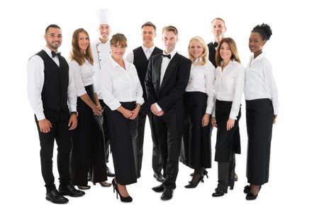 Full length portrait of confident restaurant staff standing in row against white background