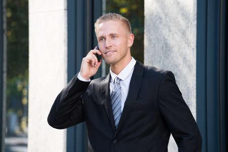 personas escuchando: Primer plano de un empresario hablando por tel�fono celular Foto de archivo