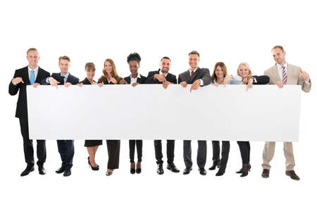 Full length portrait of happy business team pointing at blank billboard against white background Foto de archivo