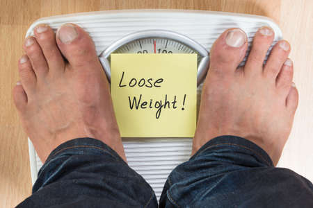 low scale: Low section of man standing on scale with loose weight sign