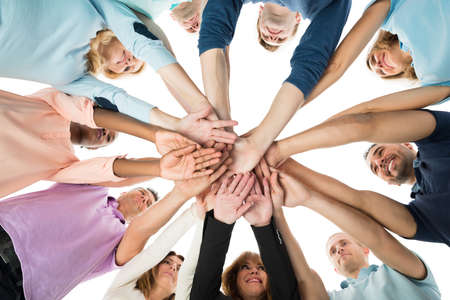 Directly below creative business team stacking hands while standing in huddle against white background