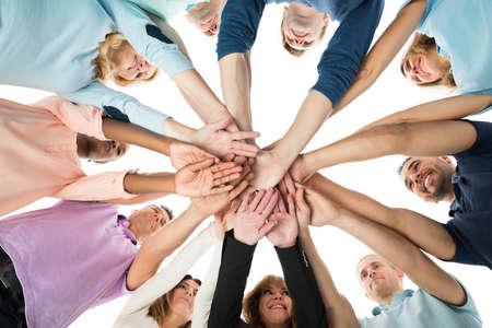 Juste en dessous de l'équipe de l'entreprise de création d'empilage des mains tout en se tenant en caucus sur le fond blanc Banque d'images
