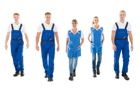 isolated man: Full length portrait of confident male and female janitors walking in row against white background