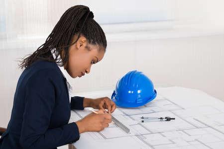 ingeniero civil: Joven Modelo gr�fico de la empresaria africana En el escritorio de oficina Foto de archivo