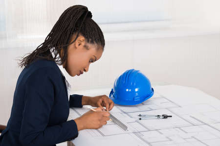 female engineer: Young African Businesswoman Drawing Blueprint At Office Desk
