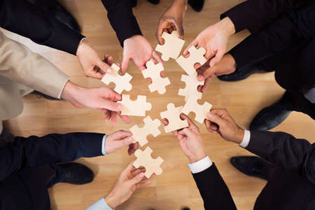 Directly above shot of business team joining jigsaw pieces in office