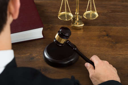 High angle view of male judge hitting mallet at desk in courtroom Stock Photo