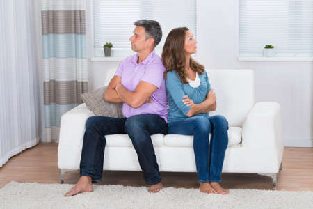 couple on couch: Unhappy Mature Couple With Armcrossed Sitting On Sofa After Quarrel