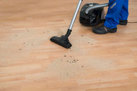 janitor: Low section of male janitor cleaning floor with vacuum cleaner in living room
