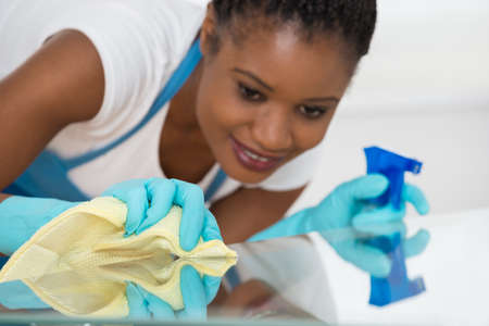 service desk: Close-up Of Young African Woman Using Spray To Wipe Glass Desk