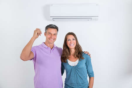 Portrait Of Happy Couple Standing In Front Of Air Conditioner With Remote In Mans Hand