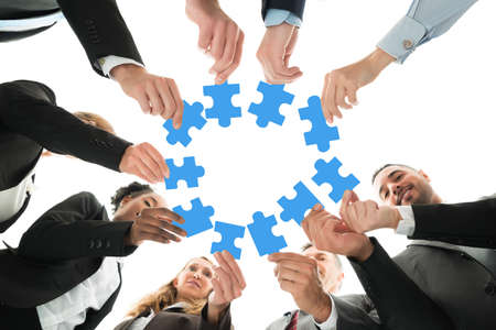 directly below: Directly below shot of business team joining jigsaw pieces in huddle against white background Stock Photo