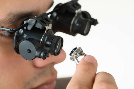 jeweler: Closeup of jeweler examining diamond ring with magnifying loupe against white background
