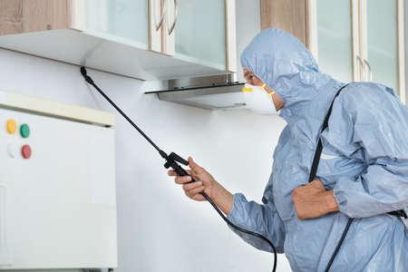 Zijaanzicht van verdelger in werkkleding het spuiten van bestrijdingsmiddelen in de keuken. Ongediertebestrijding