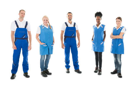 Cleaning team: Full length portrait of confident multiethnic janitors standing in row against white background