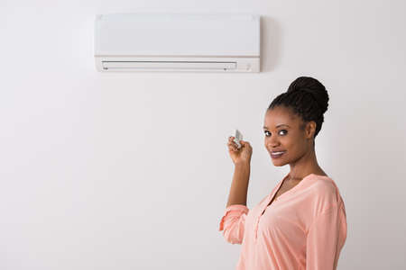 Young African Woman Operating Air Conditioner With Remote Control