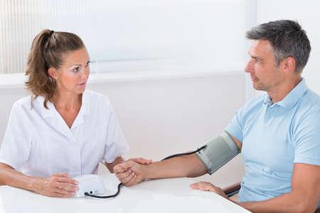high blood pressure: Female Doctor Measuring Blood Pressure Of Man In Hospital
