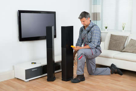 surround: Full length of technician checking TV speaker with multimeter at home