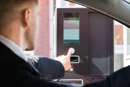 persona seduta: Person Sitting In Car Using Parking Machine To Pay For Parking