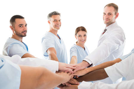 piling: Portrait of smiling medical team piling hands while standing against white background