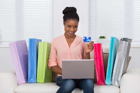 payments: Young African Woman Using Card While Shopping Online On Laptop With Bags On Sofa