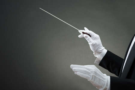 orchestra: Cropped image of music conductors hand instructing with baton against gray background