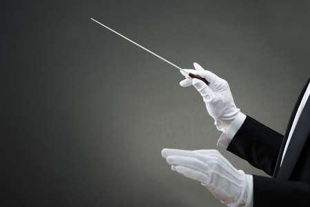 orquesta: Imagen recortada de la mano del conductor de la m�sica instruyendo con el bast�n contra el fondo gris Foto de archivo