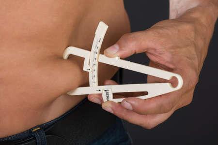 gordos: Primer plano del hombre que mide la grasa del estómago con la pinza contra el fondo gris Foto de archivo