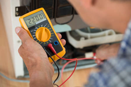 appliance: Cropped image of male repairman checking fridge with digital multimeter at home
