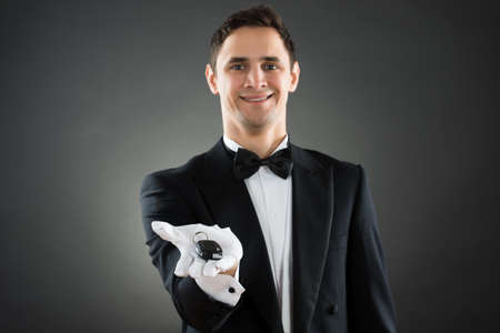 bowtie: Portrait of happy young waiter giving car keys against gray background Stock Photo