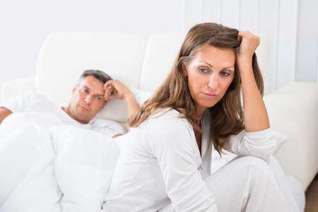 descansando: Mujer trastornada que se sienta en la cama con el hombre en el fondo