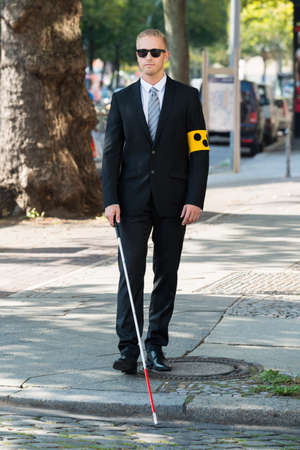 depend: Blind Man Walking On Sidewalk Holding Stick Wearing Armband