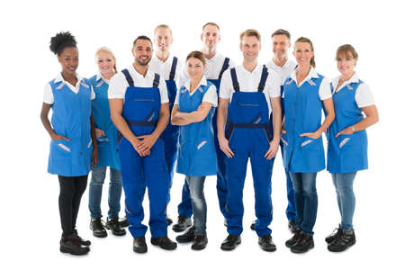 Cleaning team: Group portrait of confident male and female janitors standing against white background Stock Photo