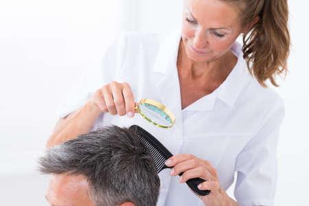 piojos: Mujer dermatólogo Mirando a pelo del paciente a través de la lupa Foto de archivo