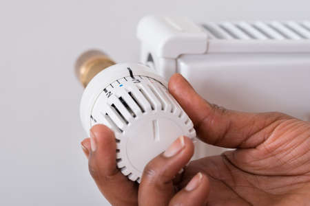 torridity: Close-up Of Persons Hand Holding Radiator Thermostat Stock Photo