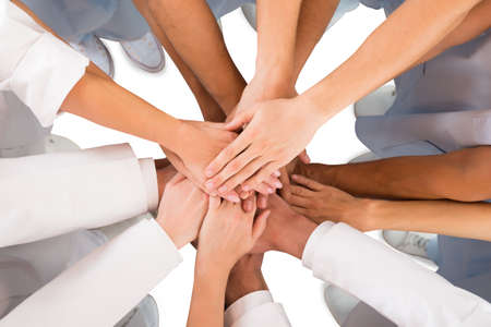 group of hands: Directly above shot of medical team standing hands against white background Stock Photo